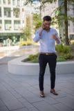 Επιτυχής νέος επιχειρηματίας που μιλά στο smartphone του έξω στοκ εικόνες