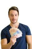 Επιτυχής νεαρός άνδρας που εξετάζει τα ευρο- τραπεζογραμμάτια Στοκ Φωτογραφίες