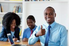 Επιτυχής οικονομικός σύμβουλος αφροαμερικάνων με την επιχειρησιακή ομάδα στοκ εικόνα