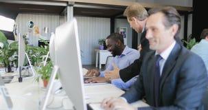 Επιτυχής ομάδα επιχειρηματιών φυλών μιγμάτων που εργάζεται στο σύγχρονο coworking κέντρο χρησιμοποιώντας τους υπολογιστές και συζ απόθεμα βίντεο