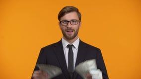 Επιτυχής πλούσιος άνθρωπος που παρουσιάζει δέσμη των δολαρίων και του εύκολου εισοδήματος κλεισίματος του ματιού στο διαδίκτυο φιλμ μικρού μήκους