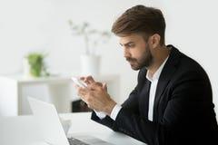 Επιτυχής σοβαρός επιχειρηματίας που χρησιμοποιεί το smartphone apps για την επιχείρηση Στοκ Εικόνες