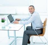 Επιτυχής χαμογελώντας επιχειρηματίας που εργάζεται στο lap-top στο γραφείο στο offi Στοκ φωτογραφία με δικαίωμα ελεύθερης χρήσης