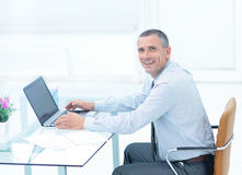 Επιτυχής χαμογελώντας επιχειρηματίας που εργάζεται στο lap-top στο γραφείο στο offi Στοκ Εικόνα