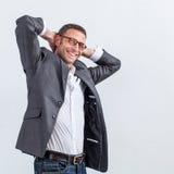 Επιτυχής χαμογελώντας όμορφος επιχειρηματίας που στέκεται με τα όπλα πίσω από το κεφάλι του Στοκ φωτογραφία με δικαίωμα ελεύθερης χρήσης