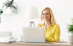 Επιτυχής ώριμη επιχειρηματίας που χρησιμοποιεί το lap-top, εργασία στην αρχή στοκ εικόνα με δικαίωμα ελεύθερης χρήσης