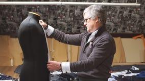 Επιτυχής ώριμος ράφτης με τη μέτρηση της ταινίας που ρυθμίζει το υλικό σχέδιο στο μανεκέν Διαδικασία το σακάκι απόθεμα βίντεο