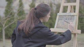 Επιτυχή χρώματα καλλιτεχνών στον καμβά στο κατώφλι Όμορφο ενθουσιώδες κορίτσι που συμμετέχεται στη δημιουργικότητα Ακαδημία τέχνη απόθεμα βίντεο