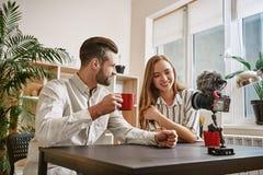 Επιτυχή bloggers Bloggers χαμόγελου που πίνουν ένα τσάι κάνοντας το νέο περιεχόμενο για το blog τους στοκ εικόνα