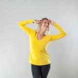 Επιτυχία για τη χαμογελώντας προκλητική ξανθή γυναίκα με το κίτρινο πουκάμισο Στοκ φωτογραφία με δικαίωμα ελεύθερης χρήσης