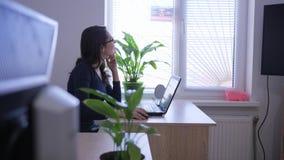 Επιτυχείς γυναίκες που εργάζονται με το lap-top στο γραφείο στο εσωτερικό κοντά στο παράθυρο και τα εσωτερικά λουλούδια φιλμ μικρού μήκους