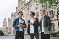 Επιτυχείς ευτυχείς σπουδαστές που στέκονται κοντά στην πανεπιστημιούπολη ή το πανεπιστήμιο έξω Στοκ Φωτογραφίες