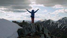Επιτυχείς νέες ανοικτές αγκάλες γυναικών backpacker στην αιχμή βουνών απόθεμα βίντεο