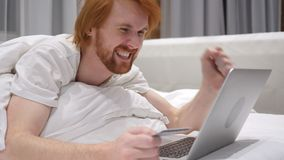 Επιτυχείς σε απευθείας σύνδεση αγορές από το Redhead άτομο γενειάδων στο κρεβάτι, πιστωτική κάρτα απόθεμα βίντεο