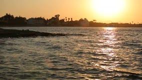 Επιφάνεια θάλασσας και sillouette παραλιών στο ηλιοβασίλεμα φιλμ μικρού μήκους
