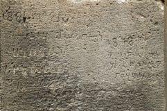 Επιφάνεια του αρχαίου τοίχου πετρών με τις μεσαιωνικά γραφές και τα ψηφία Στοκ φωτογραφία με δικαίωμα ελεύθερης χρήσης