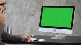 Επιχείρηση, άνθρωποι, έννοια επικοινωνίας και τεχνολογίας - επιχειρηματίας με τον υπολογιστή που καλεί το smartphone στο γραφείο φιλμ μικρού μήκους