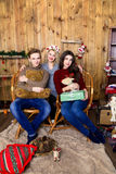 Επιχείρηση αγοριού και δύο κοριτσιών με τα δώρα στο δωμάτιο με ξύλινο Στοκ Εικόνες
