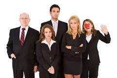 Επιχείρηση: Γυναίκα με τη μύτη κλόουν που έχει τη διασκέδαση με τη σοβαρή ομάδα στοκ εικόνα