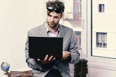 Επιχείρηση και έννοια τεχνολογιών Επιχειρηματίας με το lap-top και το σωρό των βιβλίων στο υπόβαθρο παραθύρων Στοκ Εικόνες
