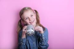 Επιχείρηση και έννοια χρημάτων - ευτυχές μικρό κορίτσι με τα ευρο- χρήματα μετρητών πέρα από το ρόδινο υπόβαθρο στοκ εικόνες