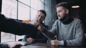 Επιχείρηση τριών φίλων που διοργανώνουν μια ενεργό συζήτηση καθμένος στο φραγμό, γελούν και αυξάνουν τα γυαλιά τους απόθεμα βίντεο