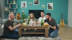 Επιχείρηση των αγοριών και των κοριτσιών που παίζουν το επιτραπέζιο παιχνίδι στο καθιστικό και που πίνουν την μπύρα φιλμ μικρού μήκους