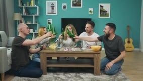 Επιχείρηση των αγοριών και των κοριτσιών που παίζουν το επιτραπέζιο παιχνίδι στο καθιστικό και που πίνουν την μπύρα απόθεμα βίντεο