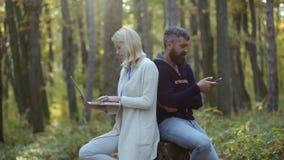 Επιχείρηση υπαίθρια Ζεύγος που εργάζεται - που χρησιμοποιεί το lap-top και το smartphone υπαίθρια Άνθρωποι ερωτευμένοι στο υπόβαθ απόθεμα βίντεο