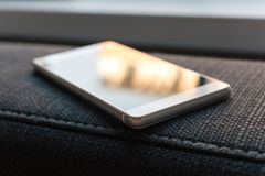 Επιχείρηση Smartphone με την αντανάκλαση που βρίσκεται Armrest ενός καναπέ Στοκ Εικόνες