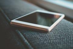 Επιχείρηση Smartphone που βρίσκεται Armrest ενός καναπέ Στοκ φωτογραφία με δικαίωμα ελεύθερης χρήσης