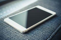 Επιχείρηση Smartphone που βρίσκεται Armrest ενός καναπέ Στοκ εικόνα με δικαίωμα ελεύθερης χρήσης