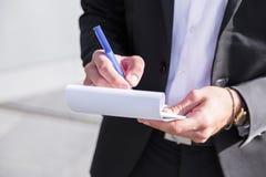 Επιχειρηματίας ή εργαζόμενος αρσενικών στο μαύρο κοστούμι που γράφει στο σημειωματάριο Στοκ Φωτογραφία