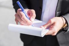 Επιχειρηματίας ή εργαζόμενος αρσενικών στο μαύρο κοστούμι που γράφει στο σημειωματάριο Στοκ φωτογραφία με δικαίωμα ελεύθερης χρήσης