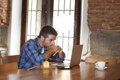 Επιχειρηματίας ή σπουδαστής που εργάζεται με το φορητό προσωπικό υπολογιστή στη καφετερία που έχει το πρόγευμα Στοκ Εικόνα