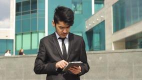 Επιχειρηματίας από την Ασία που χρησιμοποιεί την ταμπλέτα για την εργασία απόθεμα βίντεο