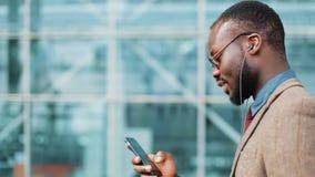 Επιχειρηματίας αφροαμερικάνων στα γυαλιά ηλίου που μιλούν στο τηλέφωνο με τα ακουστικά κοντά στο κτίριο γραφείων Επιχείρηση απόθεμα βίντεο