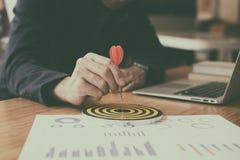 Επιχειρηματίας & x27 βέλος εκμετάλλευσης χεριών του s που χτυπά στον επιχειρησιακό στόχο Στοκ φωτογραφία με δικαίωμα ελεύθερης χρήσης