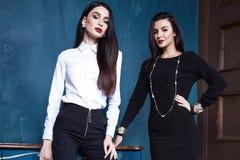 Επιχειρηματίας δύο όμορφη προκλητική γυναικών ενδυμάτων ένδυσης Στοκ Φωτογραφία