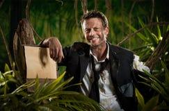 Επιχειρηματίας επιζόντων που κλίνει σε ένα σημάδι στη ζούγκλα Στοκ Φωτογραφίες