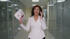 Επιχειρηματίας επιτυχίας στο κοστούμι με τα έγγραφα που μιλούν στο κινητό τηλέφωνο στο διάδρομο του γραφείου φιλμ μικρού μήκους