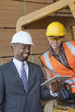 Επιχειρηματίας και γυναίκα βιομηχανικός εργάτης αφροαμερικάνων που εξετάζουν το PC ταμπλετών στοκ φωτογραφίες