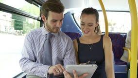 Επιχειρηματίας και γυναίκα που χρησιμοποιούν την ψηφιακή ταμπλέτα στο λεωφορείο απόθεμα βίντεο