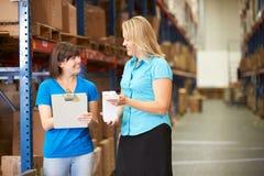 Επιχειρηματίας και γυναίκες εργαζόμενος στην αποθήκη εμπορευμάτων διανομής Στοκ φωτογραφία με δικαίωμα ελεύθερης χρήσης