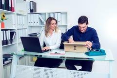 Επιχειρηματίας και επιχειρηματίας με την παράδοση στο γραφείο Στοκ Εικόνες