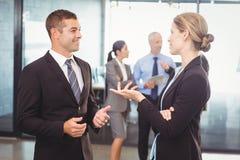 Επιχειρηματίας και επιχειρηματίας που αλληλεπιδρούν η μια με την άλλη Στοκ Εικόνες
