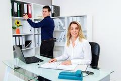 Επιχειρηματίας και επιχειρηματίας που εργάζονται μαζί στο γραφείο Στοκ εικόνα με δικαίωμα ελεύθερης χρήσης