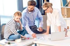 Επιχειρηματίας και επιχειρηματίας που εργάζονται με τα έγγραφα και το lap-top ενώ συνεδρίαση κορών με τα ακουστικά Στοκ εικόνες με δικαίωμα ελεύθερης χρήσης