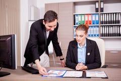 Επιχειρηματίας και επιχειρηματίας στην αρχή με τα διαγράμματα στον πίνακα Στοκ εικόνα με δικαίωμα ελεύθερης χρήσης
