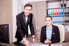 Επιχειρηματίας και επιχειρηματίας στην αρχή με τα διαγράμματα στον πίνακα Στοκ Φωτογραφίες
